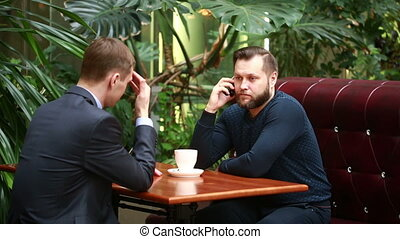 Handsome bearded businessman talking on the phone cheerfully during his coffee break on the cafe terrace. colleague is waiting for the end of the conversation