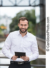 Handsome bearded businessman with a tablet