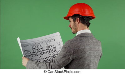 Handsome bearded engineer smiling to the camera while examining blueprints