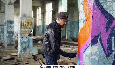 Handsome bearded guy graffiti artist is painting with spray paint inside abandoned building. Modern street art, youth subculture and creative people concept.