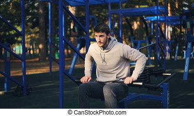 Handsome bearded guy is working out outdoors using...