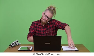 Handsome bearded hipster man multi-tasking work against...