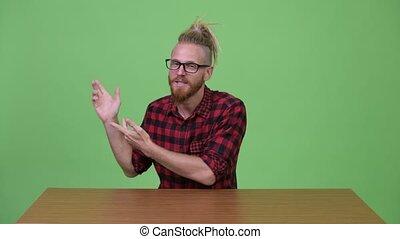 Handsome bearded hipster man presenting something against...