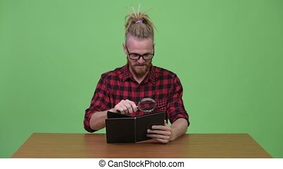 Handsome bearded hipster man reading book with magnifying...