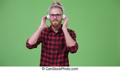 Handsome bearded hipster man with dreadlocks listening to...