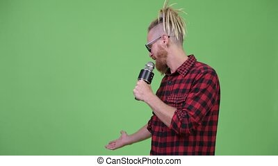 Handsome bearded hipster man with dreadlocks presenting...