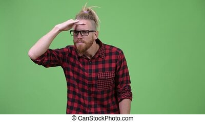 Handsome bearded hipster man with dreadlocks searching for...