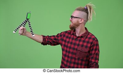 Handsome bearded hipster man with dreadlocks vlogging with...