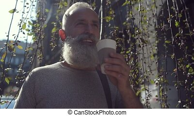 Handsome bearded man drinking delicious coffee outdoors -...