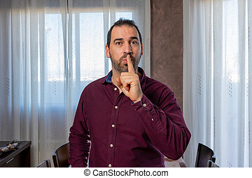 Handsome bearded man in a purple shirt making silence gesture with his index finger