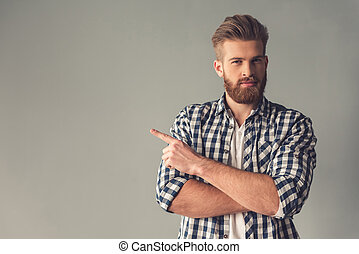 Handsome bearded man in casual clothes is pointing away,...