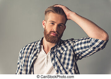 Handsome bearded man in casual clothes is smoothing his...