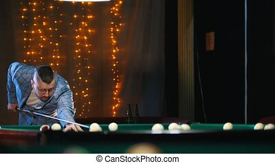 Handsome bearded man in glasses playing billiard. Mid shot