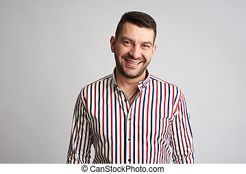 Handsome bearded man is smiling wearing a striped shirt isolated