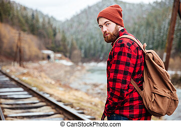 Handsome bearded man on railway road in mountains - Handsome...