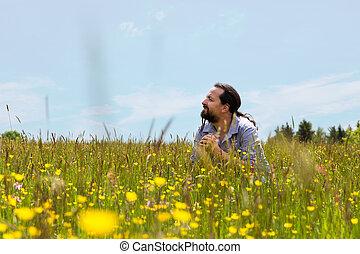 handsome bearded man sitting in a wildflower meadow