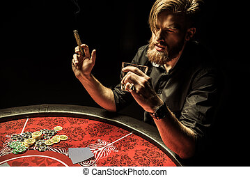 Handsome bearded man smoking cigar and drinking whisky while playing poker