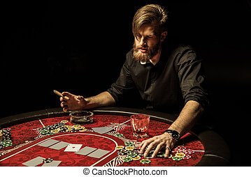 Handsome bearded man smoking cigar while playing poker at table