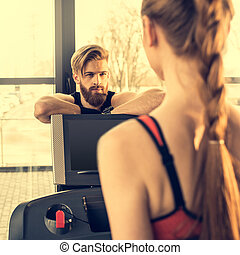 Handsome bearded man trainer looking at sporty woman exercising on treadmill