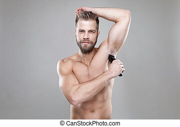 Handsome bearded man with a trimmer shaving off body hair -...