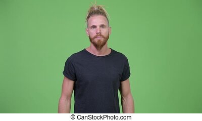 Studio shot of handsome bearded man with dreadlocks against chroma key with green background