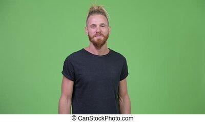 Handsome bearded man with dreadlocks smiling - Studio shot ...