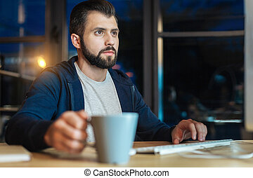 Handsome bearded man working at night