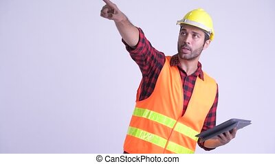 Handsome bearded Persian man construction worker directing...