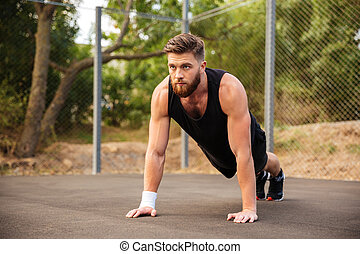 Handsome bearded sportsman doing push-ups outdoors