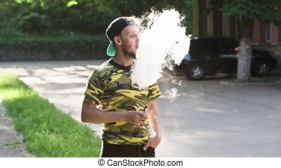 Handsome bearded young man is vaping outside - Attractive...