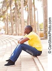 black man outdoors sitting on steps
