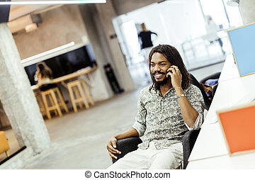 Handsome black man using phone in office