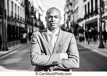 Handsome black man wearing suit in urban background - ...