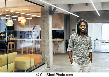 Handsome black worker standing in office