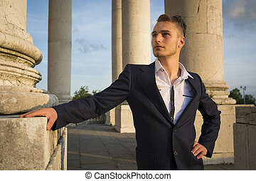 Handsome blond young man among marble columns