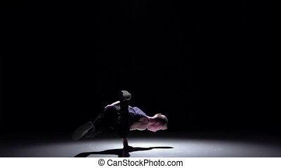 Handsome blonde breakdance style dancer continue dance, on black, shadow, slow motion