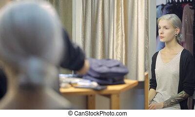 Handsome blonde woman sits in dressing room waiting for visagiste.