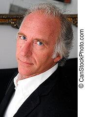 three quarter face portrait of handsome professional blue eyed older man.