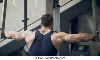 Handsome bodybuilder executes an exercise on the trainer in gym. Young sportsman raises his hands.