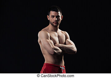 Handsome bodybuilder standing with arms folded