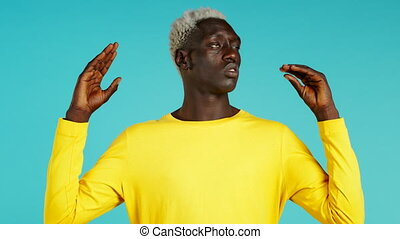 Handsome bored black man showing bla-bla-bla gesture with hands and rolling eyes isolated on blue background. Empty promises, blah concept. Lier. High quality 4k footage