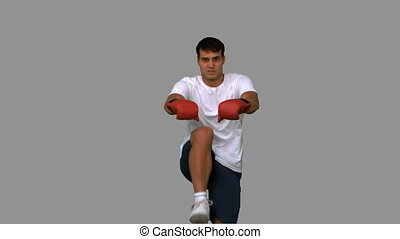 Handsome boxer performing a high kick on grey screen in slow...