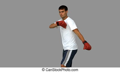 Handsome boxer performing an air kick on grey screen in slow...