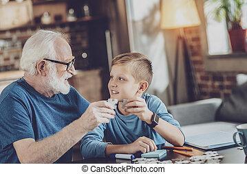 Handsome boy collecting puzzles with granddad - Happy...