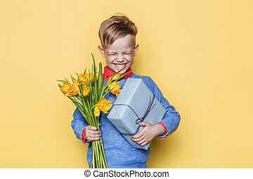 Handsome boy holding flower bunch and gift box. Valentine's day. Birthday. Mother's day. Studio portrait over yellow background