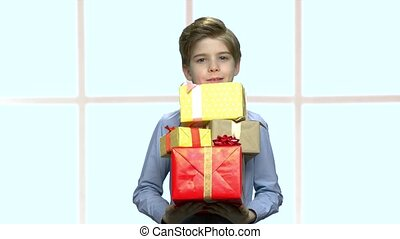 Handsome boy holding group of gift boxes.