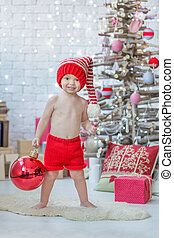 Handsome boy in red Santa Claus warm hat with big red Christmas tree toy ball celebrating New Year close to xmas tree full of presents.