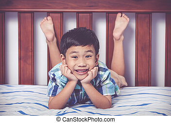 Handsome boy lying barefoot on bed in bedroom. Happy child smiling. Vintage tone effect.