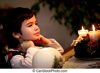 handsome boy sitting in front of candles on Christmas Eve. Christmas.