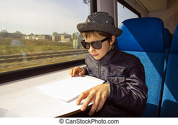 Handsome boy with sunglasses rides on a train